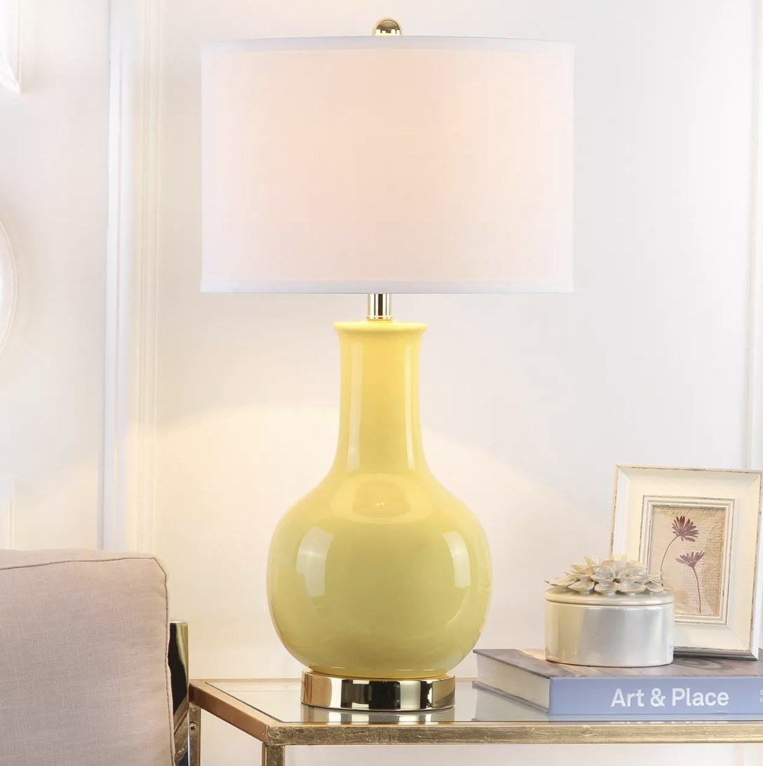 The yellow ceramic lamp has a brass colored based and bright white lampshade