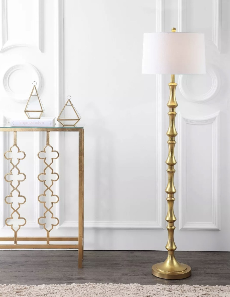 The lamp has a gold finish and turned silhouette with a white cotton shade