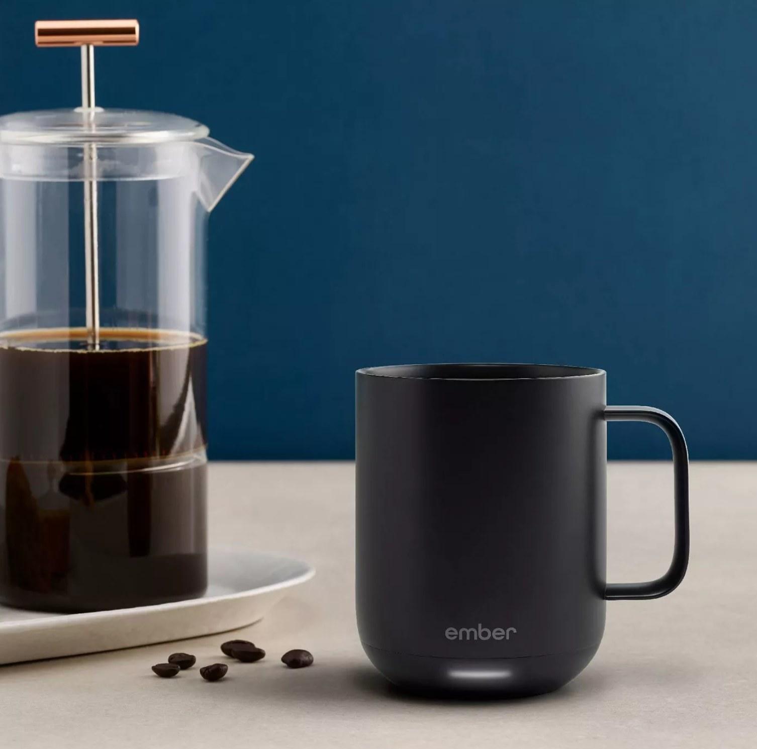 the black mug next to a coffee pot