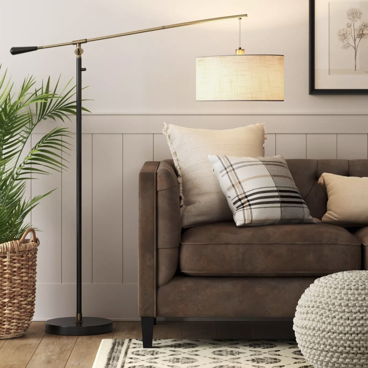 The black, gold-tone and cream lamp is overlooking a couch in a clean living room space
