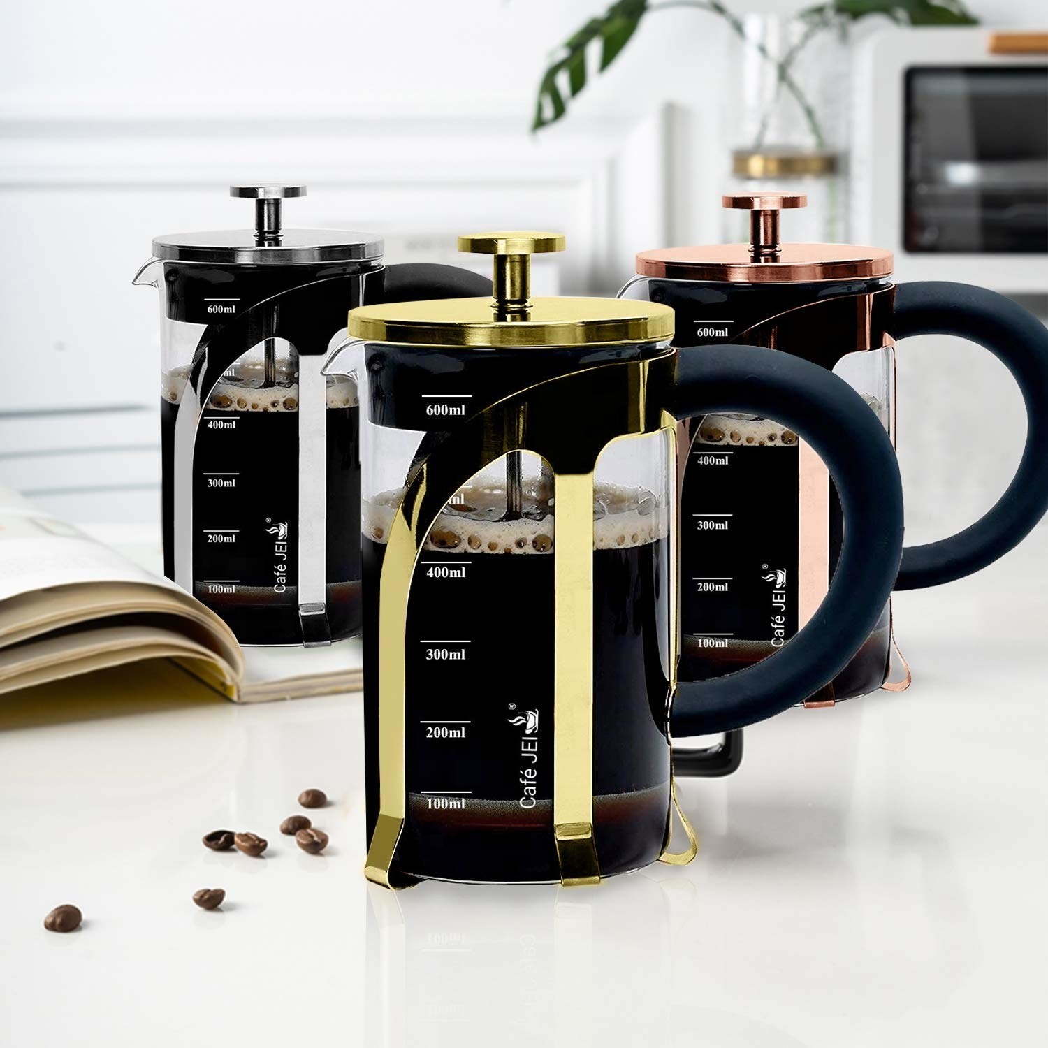 A golden, rose gold and a silver French Press coffee maker on a table