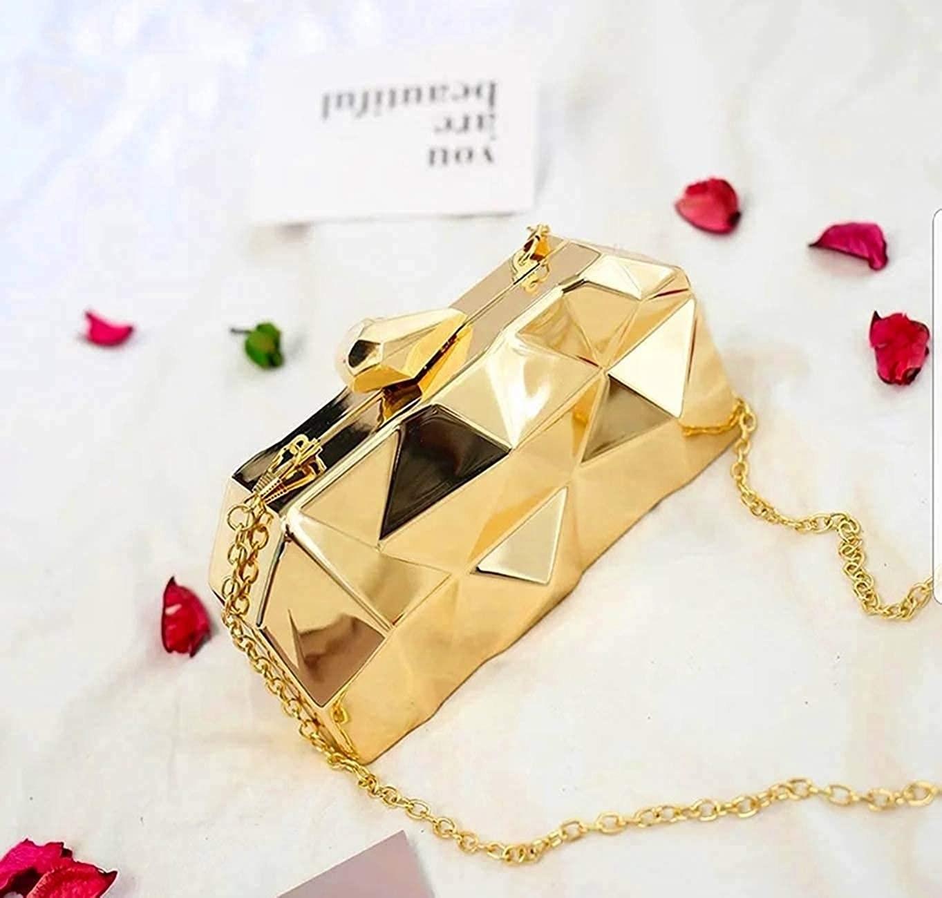 A golden clutch next to rose petals