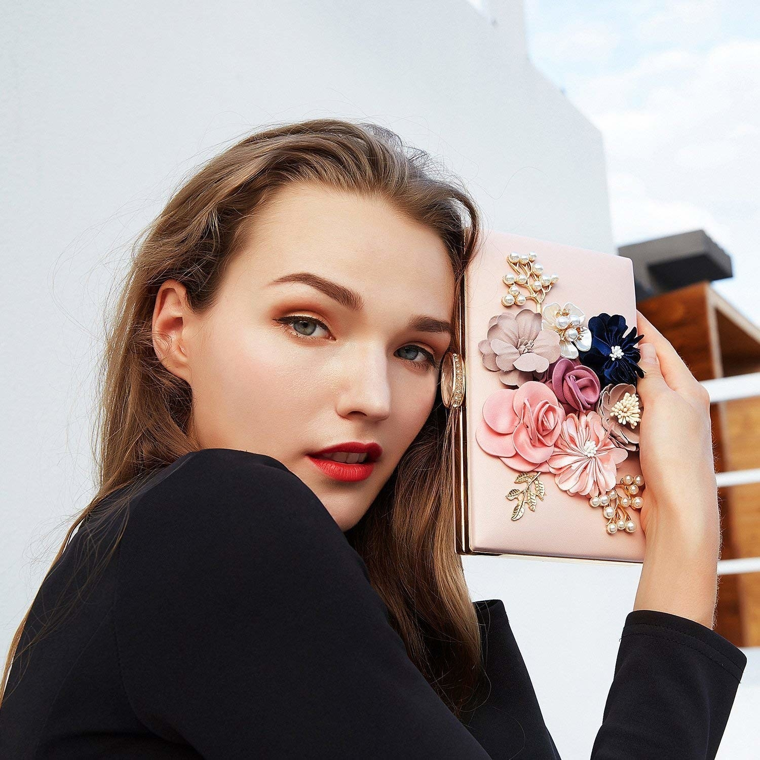 A woman holding a pink clutch bag with flowers on the front