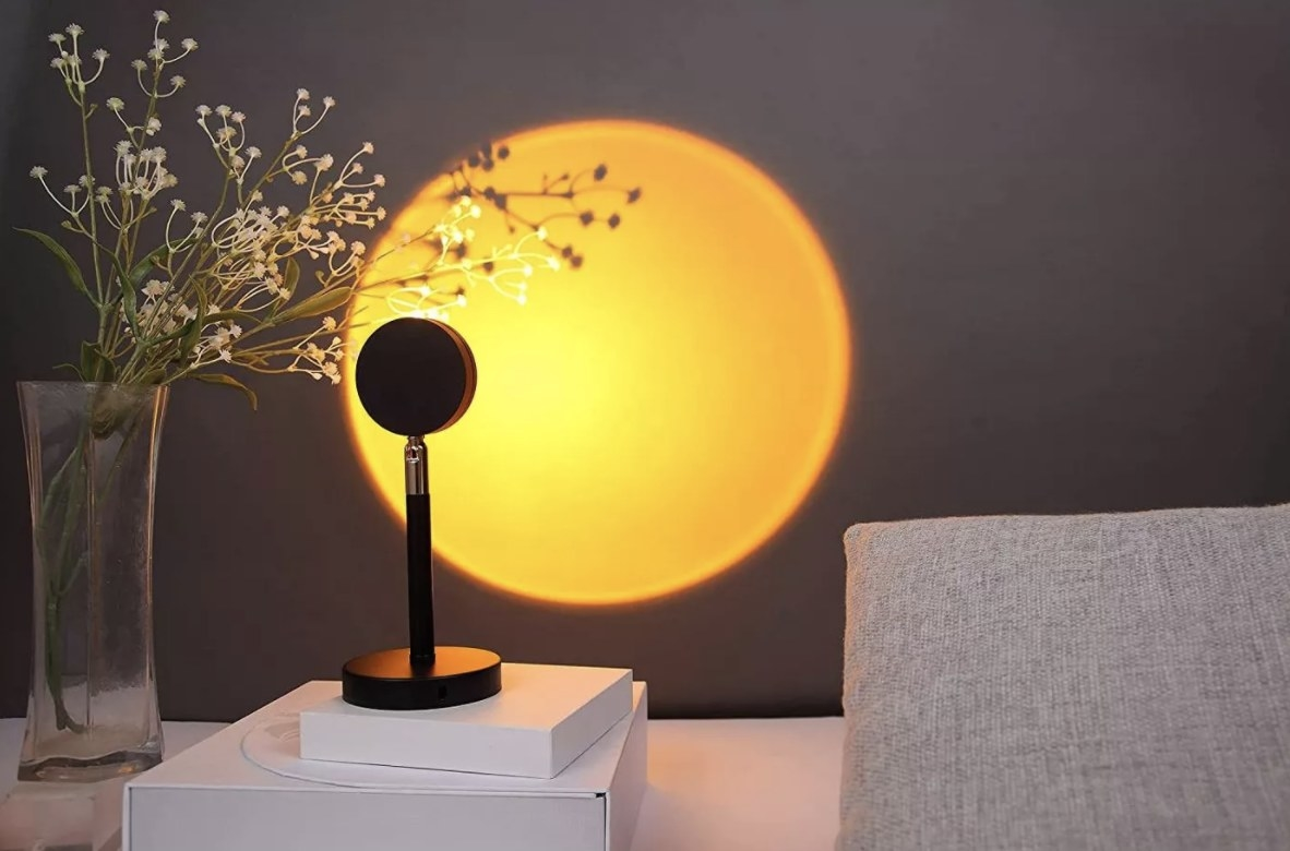 The sunset lamp is small and black and is projecting a yellow and warm spherical glow onto the wall