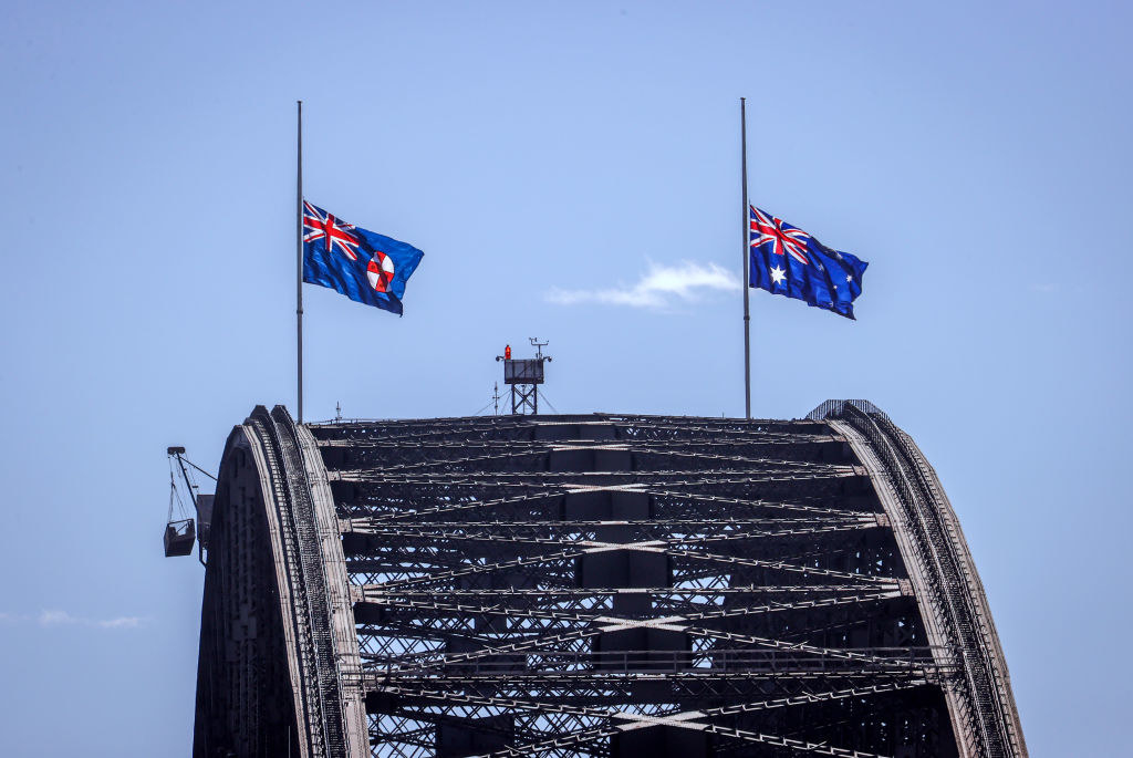 A close up of the Sydney Harbour Bridge showing the Australian National Flag and NSW State Flag