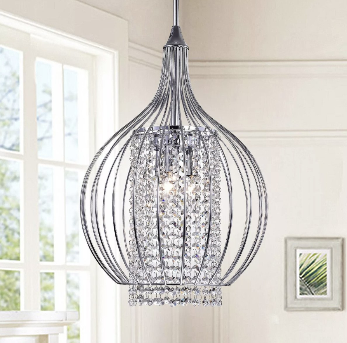 The teardrop-shaped silver frame and clear crystals in an inner cylinder frame sparkle in a well lit room