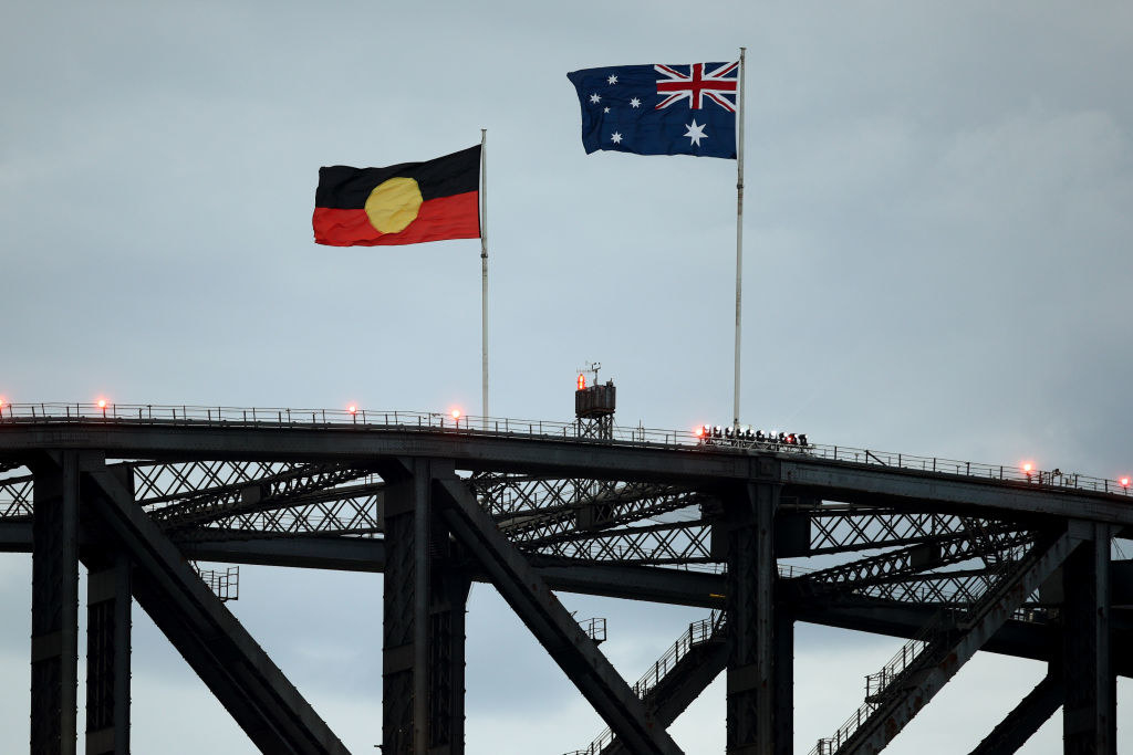 A close up of Sydney Harbour Bridge with the Australian National Flag and the Aboriginal Flag