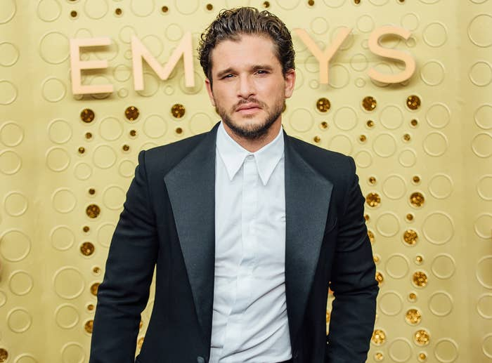 Kit looks serious while wearing a suit jacket and white button down at an event