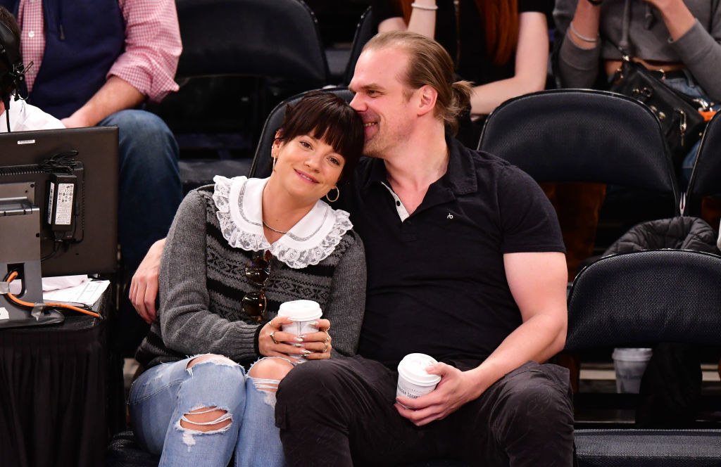 Lily Allen (L) and David Harbour cuddle at the New York Knicks v New Orleans Pelicans preseason game