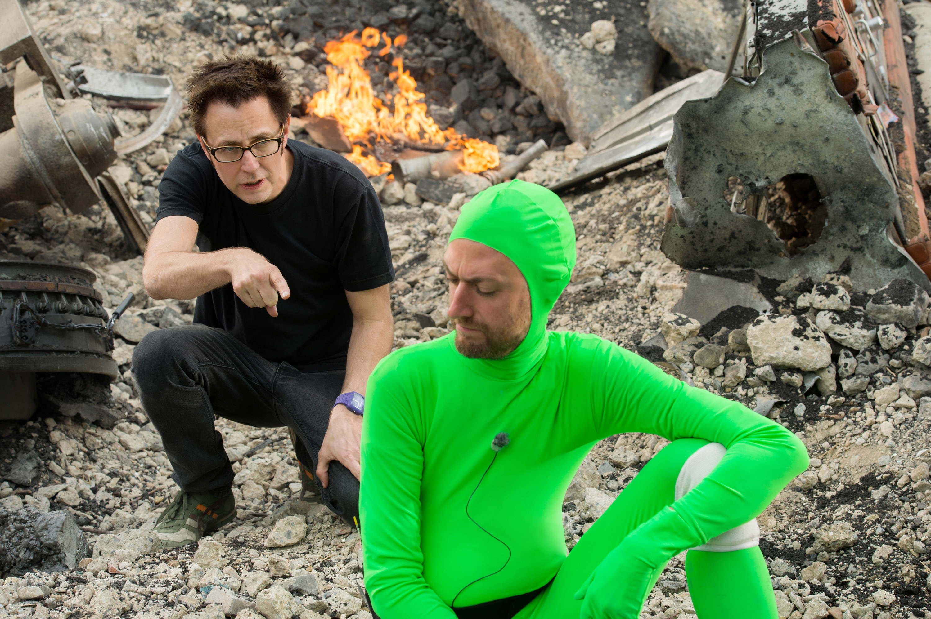 Jamescrouches down on a pile of rubble while directing an actor in a green screen suit