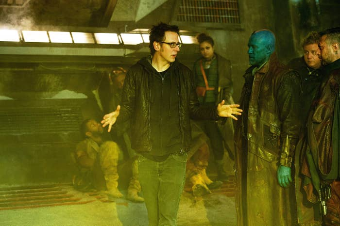 James walks through the Guardians set while talking to an extra with a blue face