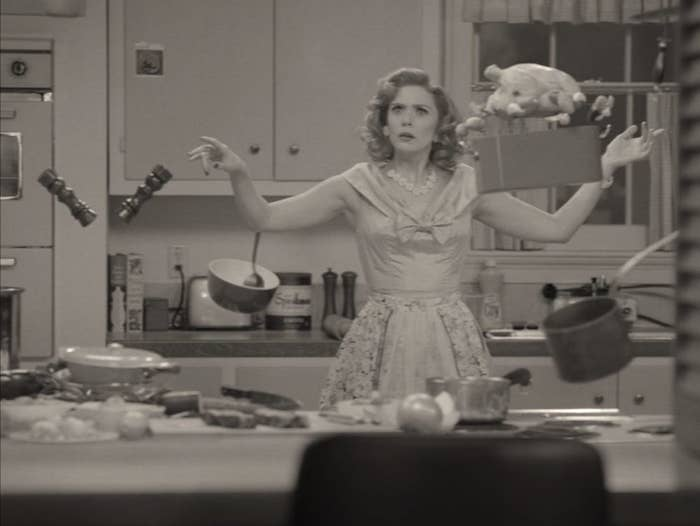 wanda maximoff in 50s womens dress in kitchen, food floating in the air