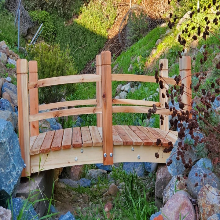 The foot bridge in a lighter stain over a ravine