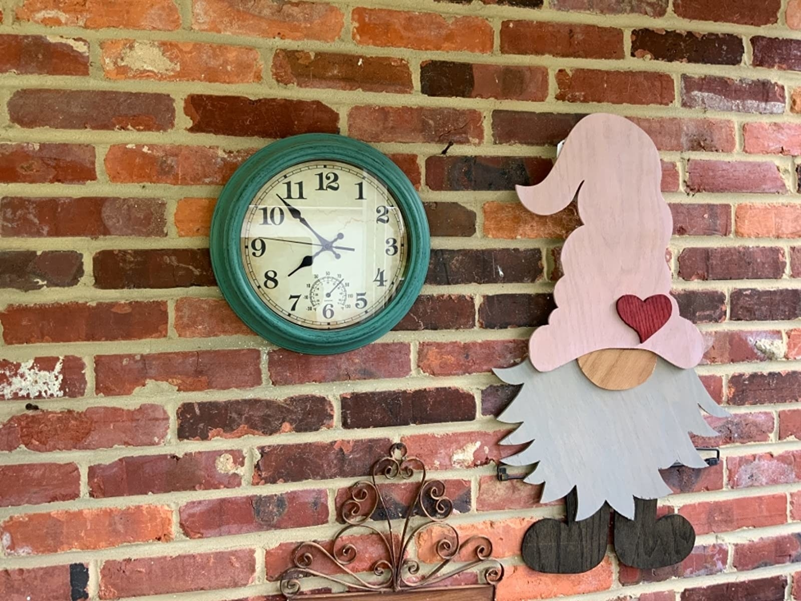 A green outdoor clock next to a gnome wall decor against a brick wall