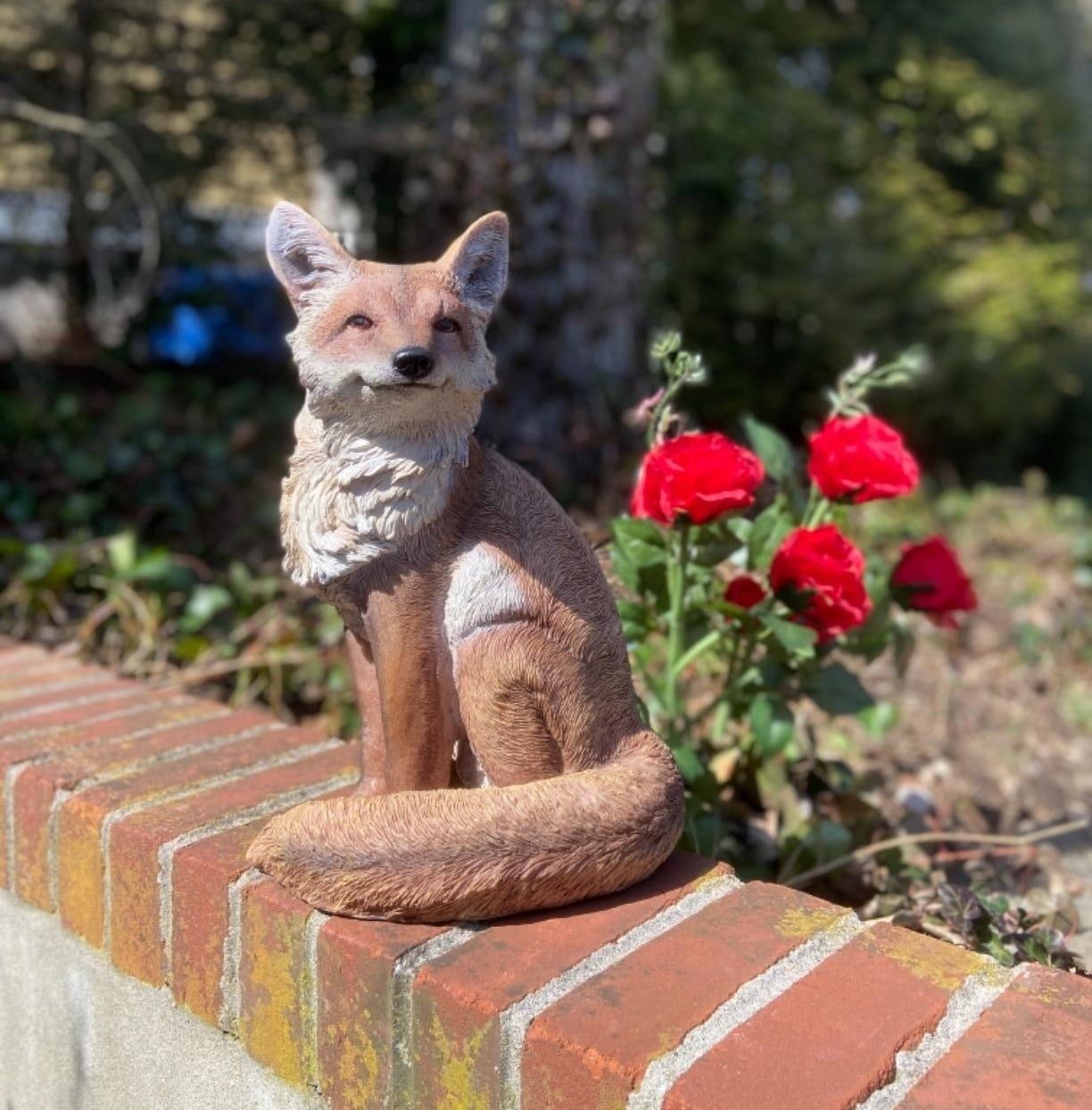 A fox statue with a calm expression placed on a stone ledge