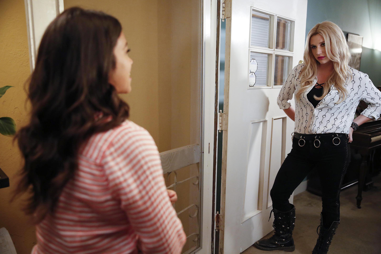 Kesha standing in a doorway, talking to Jane