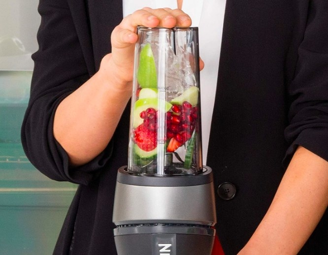 The blender mixing a fruit and ice smoothie