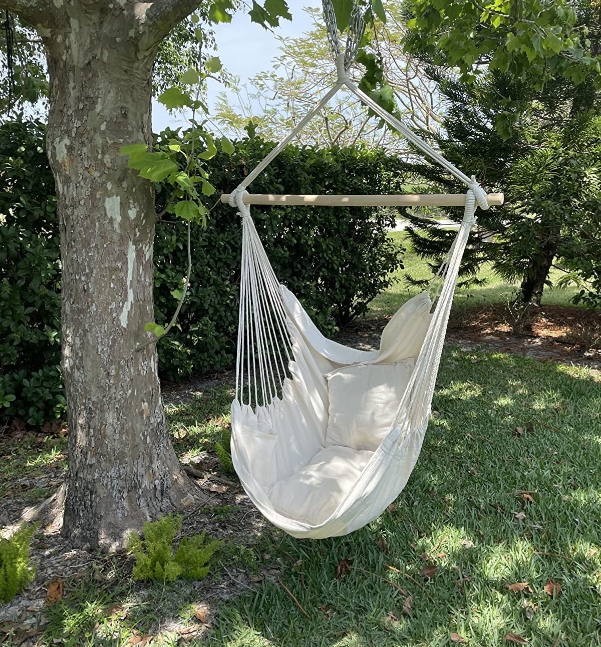 Reviewer photo of a white hammock chair hung from a tree branch