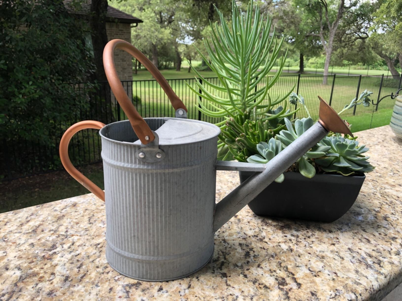 A metal watering can with copper accents sitting on a ledge