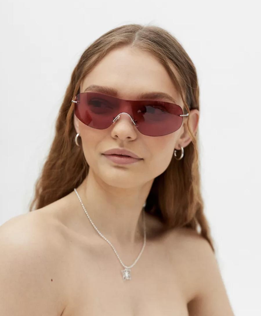 model wearing frameless red sunglasses
