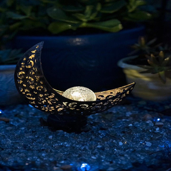 The crescent moon garden stake with an orb in the center lit up