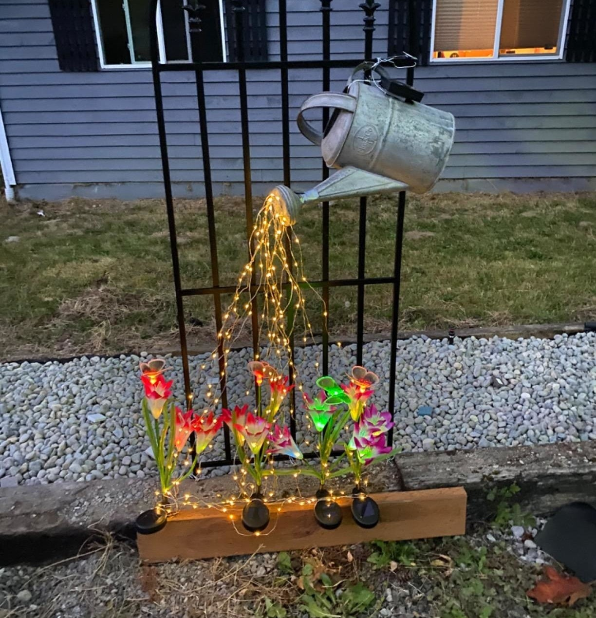 A reviewer photo of the fairy lights falling down from a watering can onto solar powered flowers