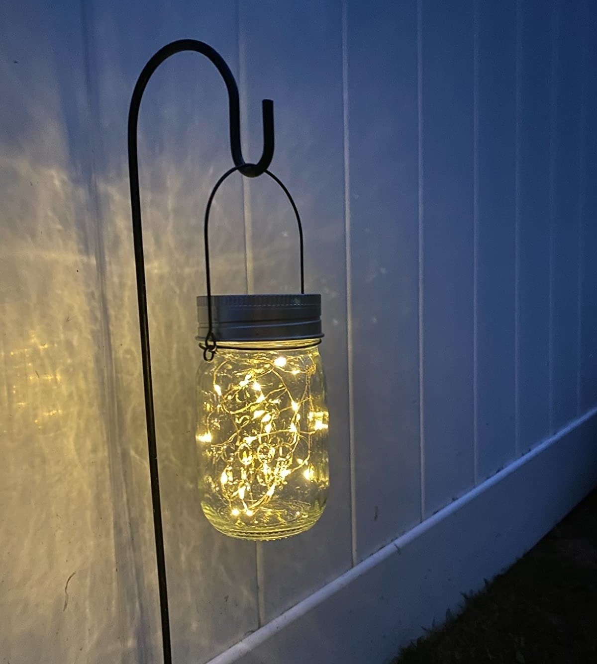A reviewer photo of a mason jar hanging off a stake with a bundle of fairy lights inside