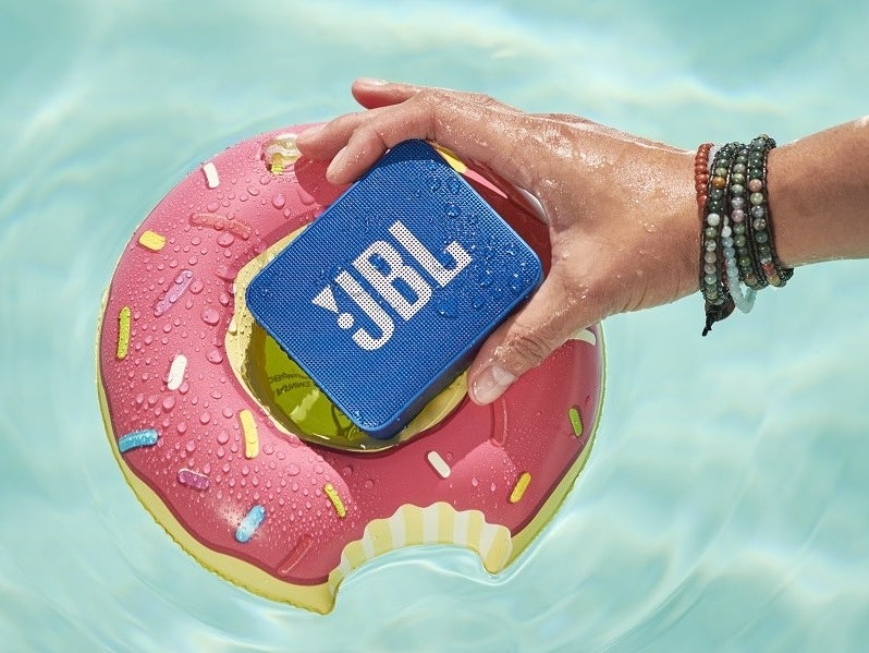 A person holding a JBL speaker in water over a donut-shaped pool float