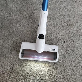 a reviewer photo of the vacuum with the headlights on