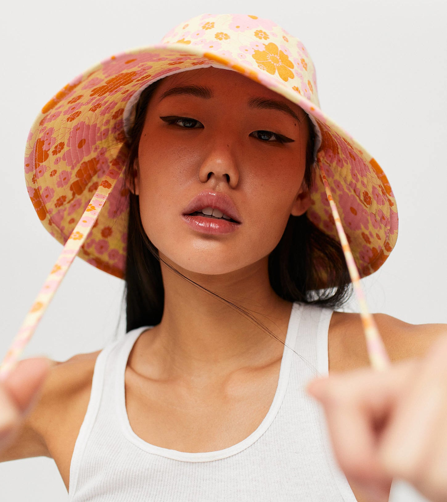 a person wearing the bucket hat and holding onto the straps
