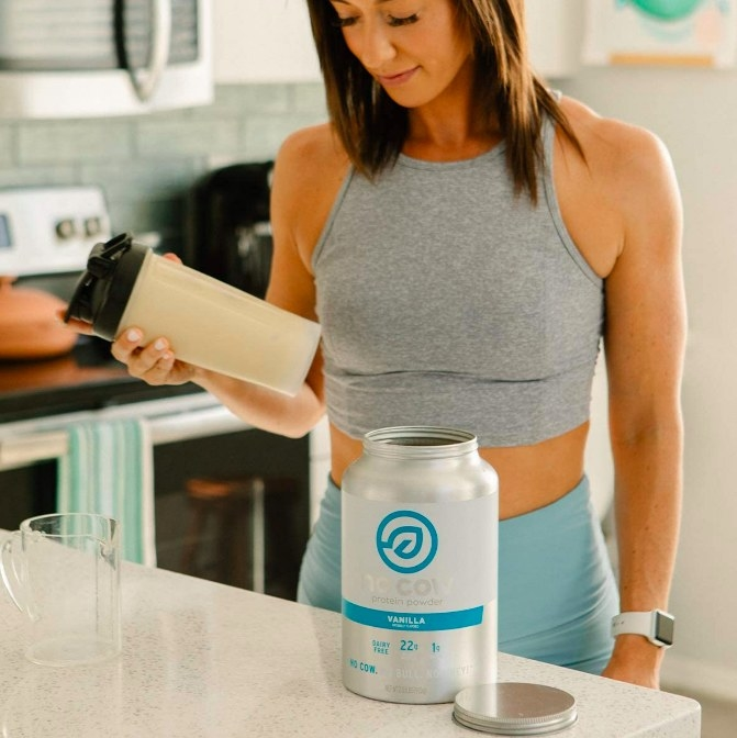 Model shaking a vanilla protein shake for a pre-workout meal