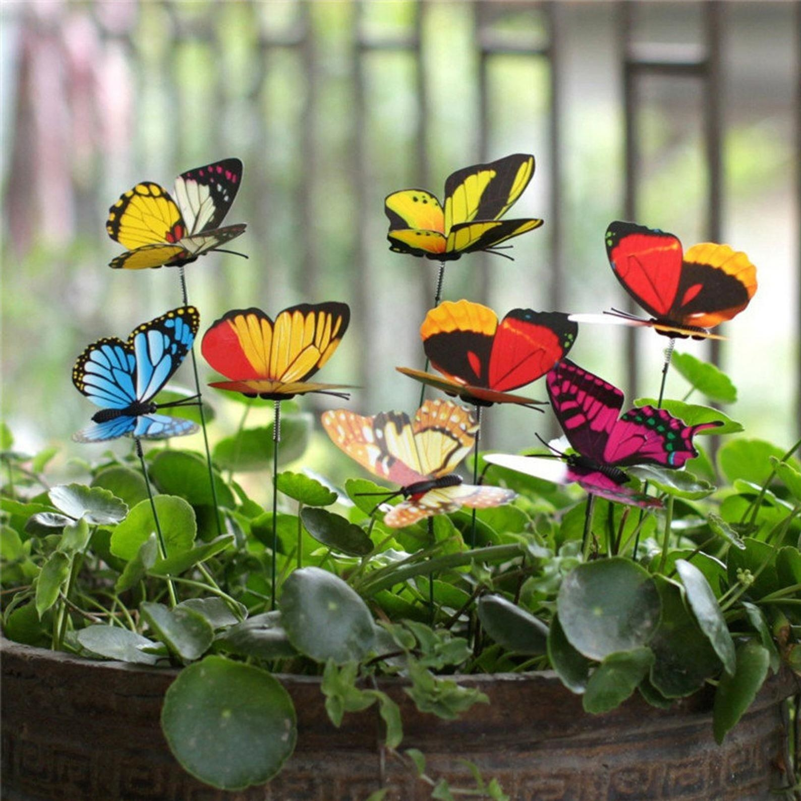 Eight colorful fake butterflies staked into a potted plant