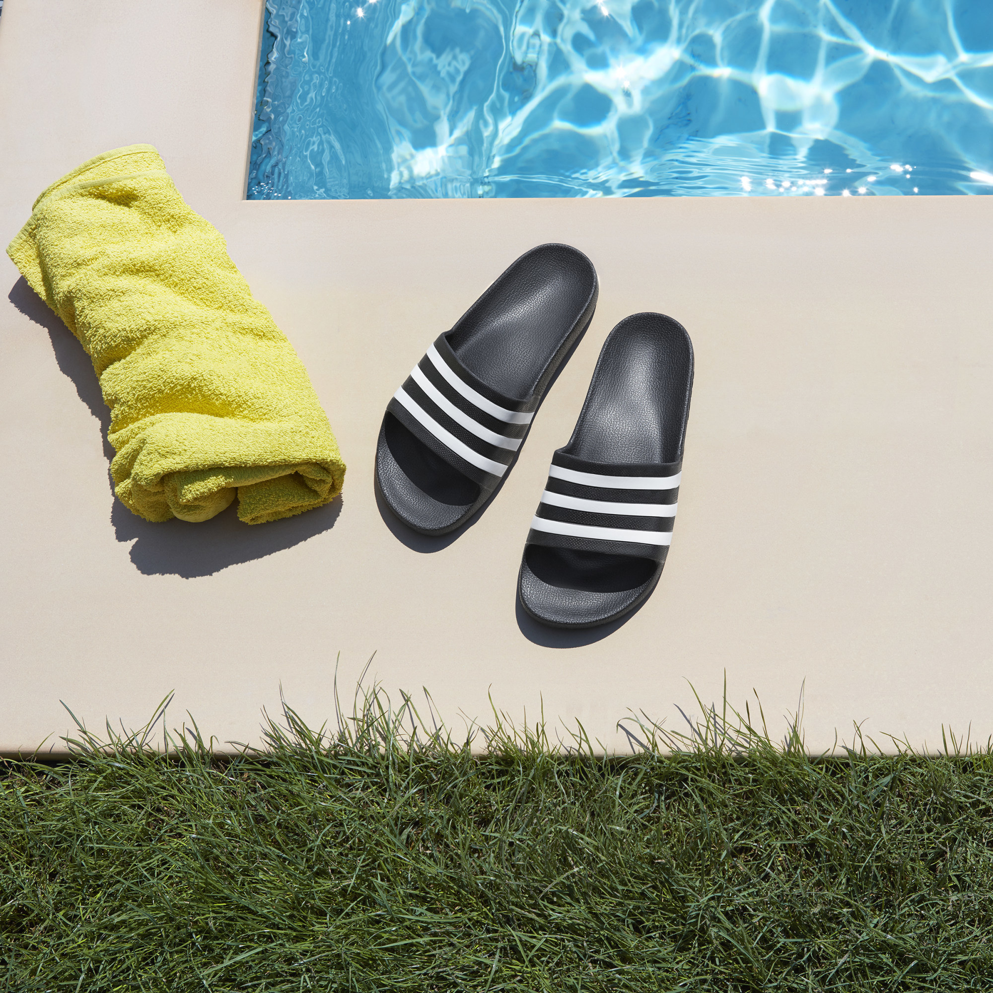 a pair of adidas aqua slides on the side of a pool beside a towel