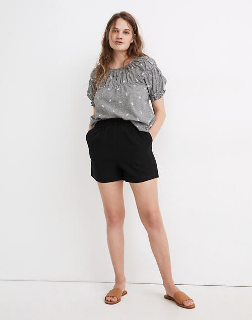 A model wears the mid-thigh shorts with their hands in the pockets