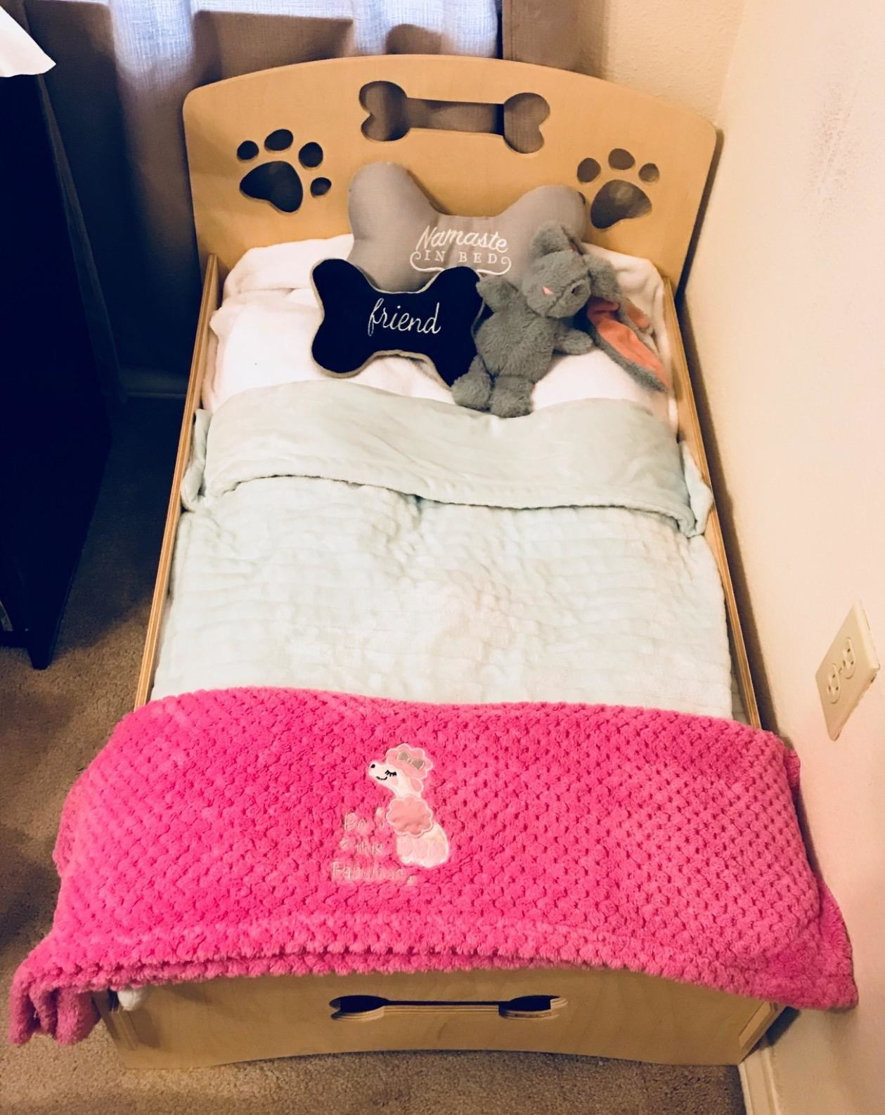 reviewer image of the wooden dog frame with pillows and sheets