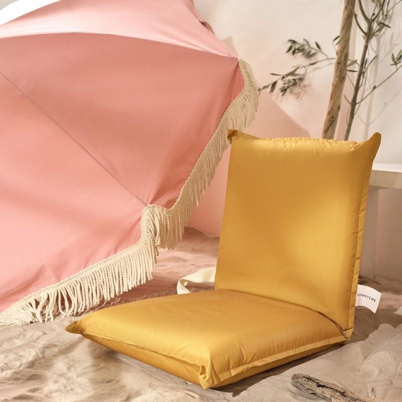 the lounge chair on a beach beside a boho umbrella