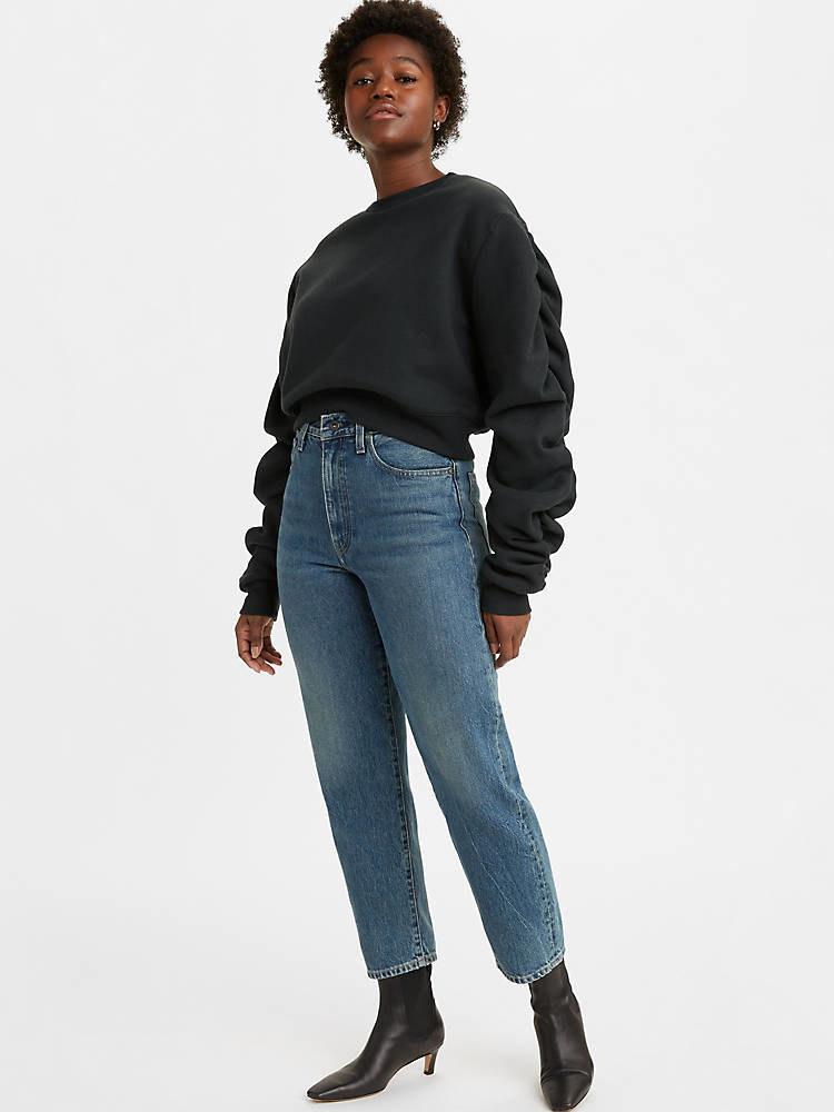 Model wearing a straight leg denim pant with heels