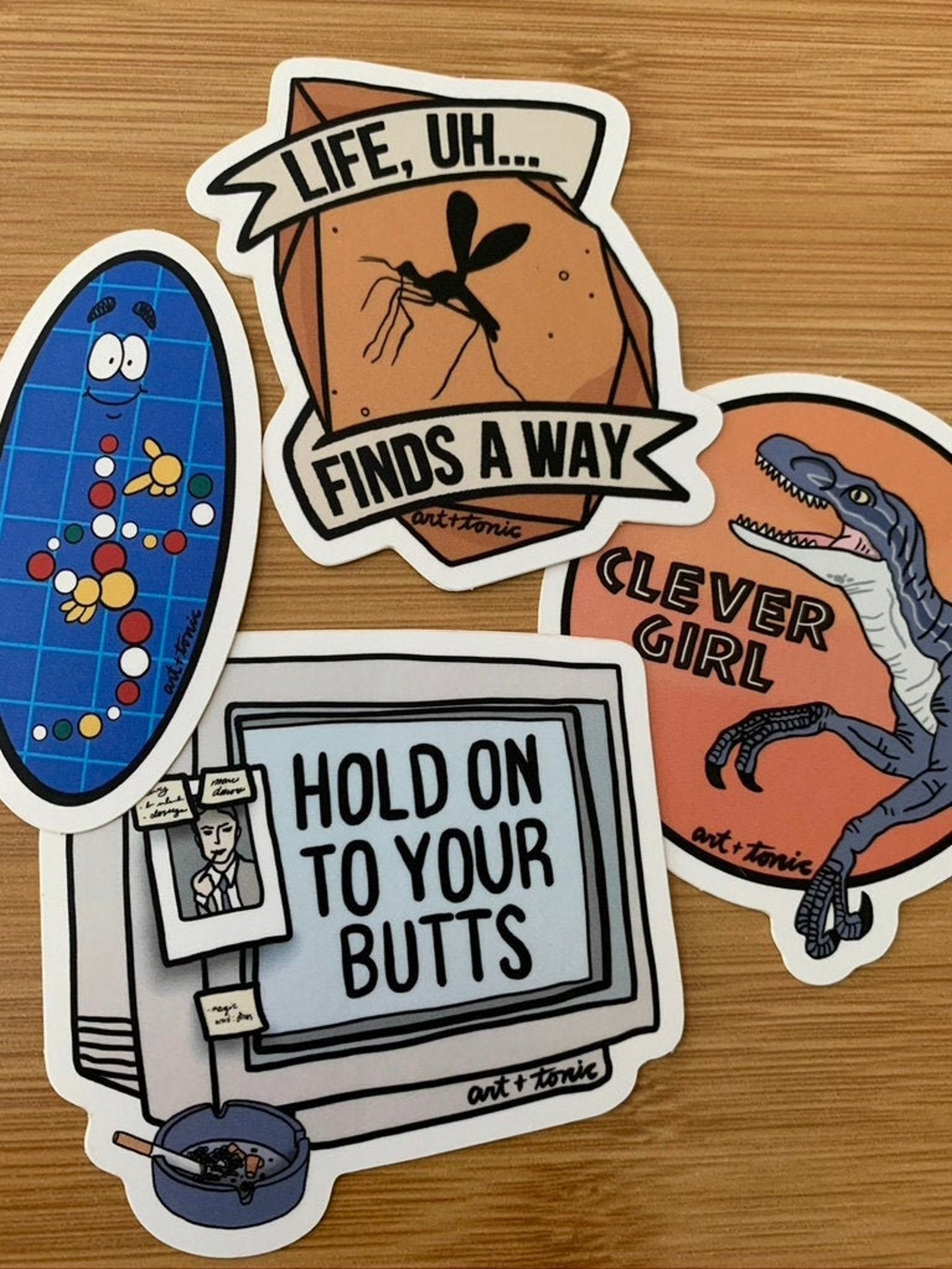 """four jurassic park stickers: one with a mosquito that says """"life, uh, finds a way"""", one with a velociraptor that says """"clever girl"""" one of a computer that says """"hold on to your butts"""" and one of the DNA illustration from the movie"""