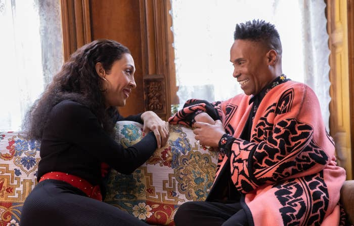 MJ and Billy sitting on a couch and smiling during a scene from pose