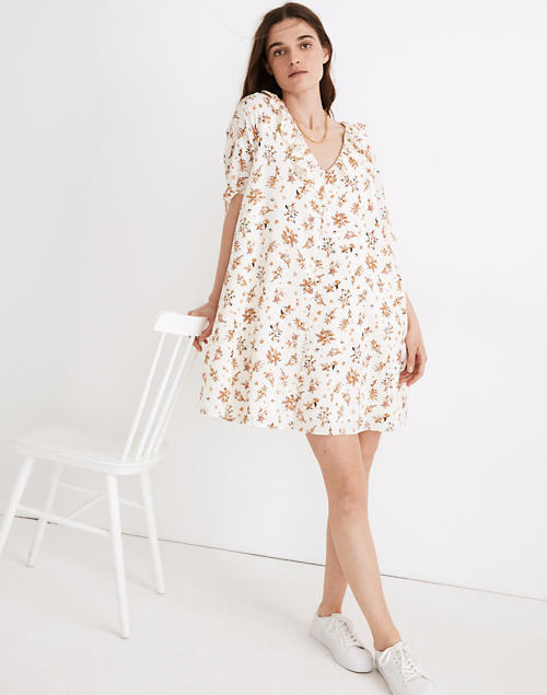 A model wears the white and floral pattern dress