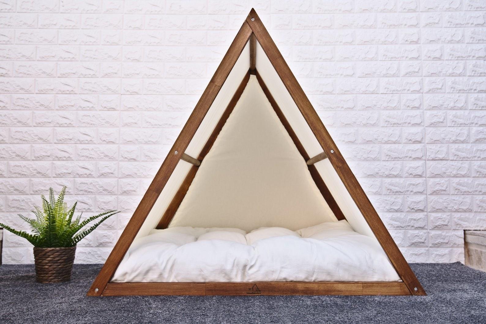a triangular walnut dog house with a white cushion inside