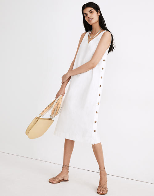 A model wears the white sleeveless dress with buttons down the side