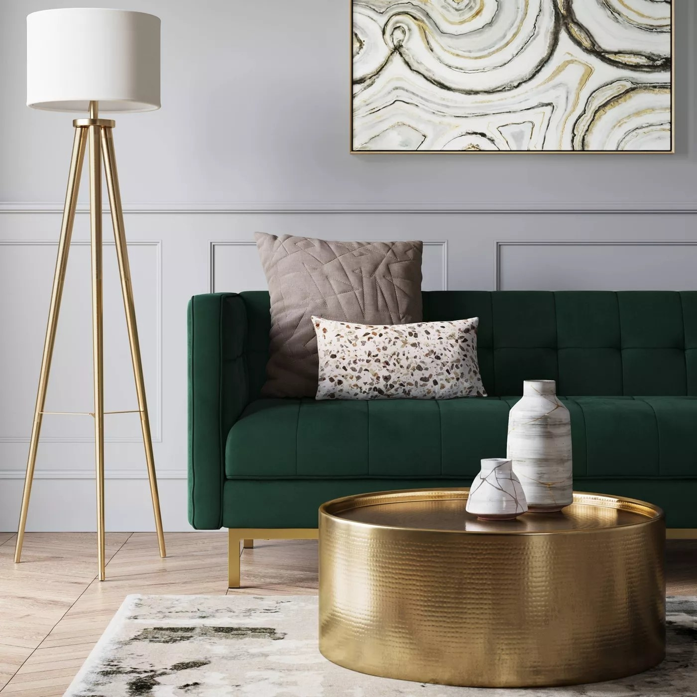 The sofa with a tufted back, seat, and sides as well as brass legs in a living room