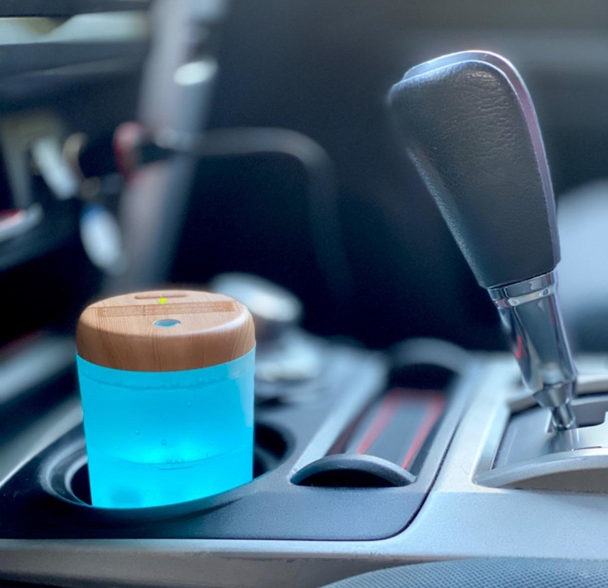 a small glowing blue diffuser in the cup holder of a reviewer's car