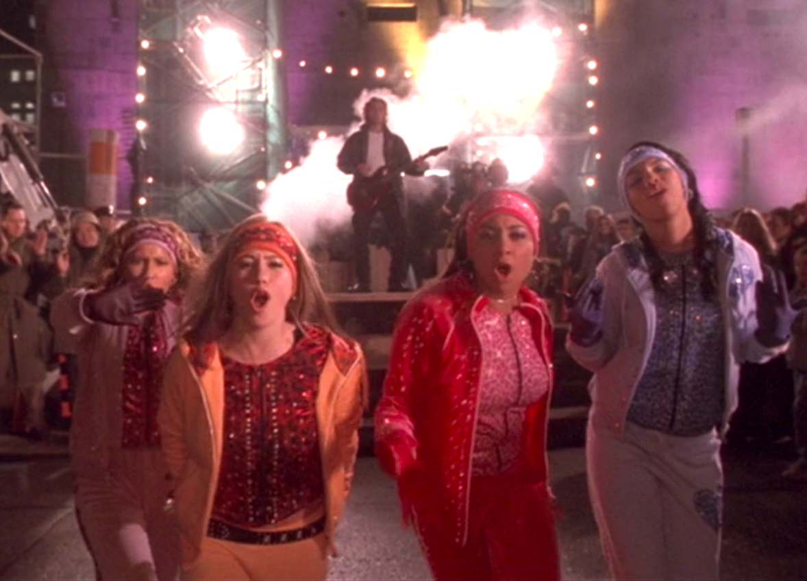 The Cheetah Girls wearing cheetah pattered outfits of different colors