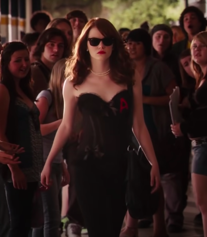 Olive wearing jeans, a corset with an A on it, a pearl necklace, and sunglasses