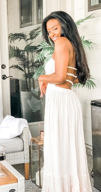 reviewer wearing the white dress showing the open strappy back detail
