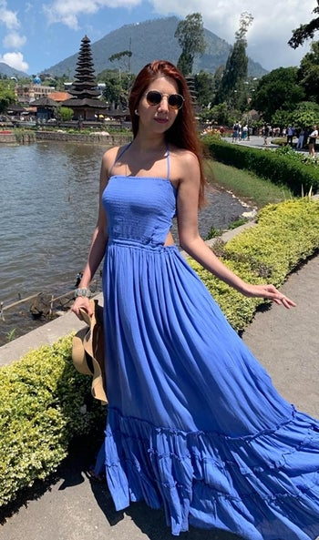 model wearing the blue maxi dress with cut outs and ruffle tier detailing on the skirt