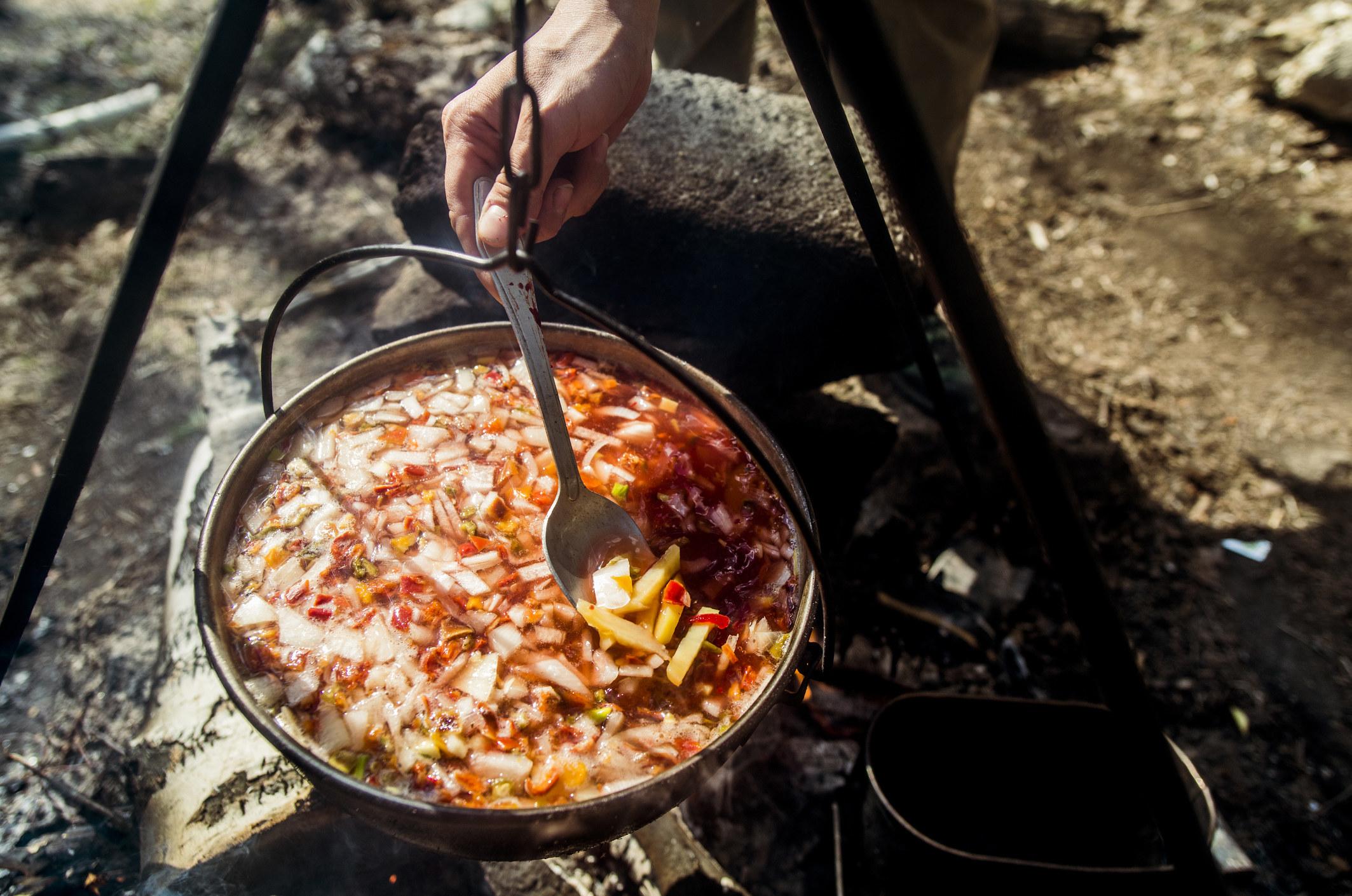 Stirring a pot of soup over a campfire.