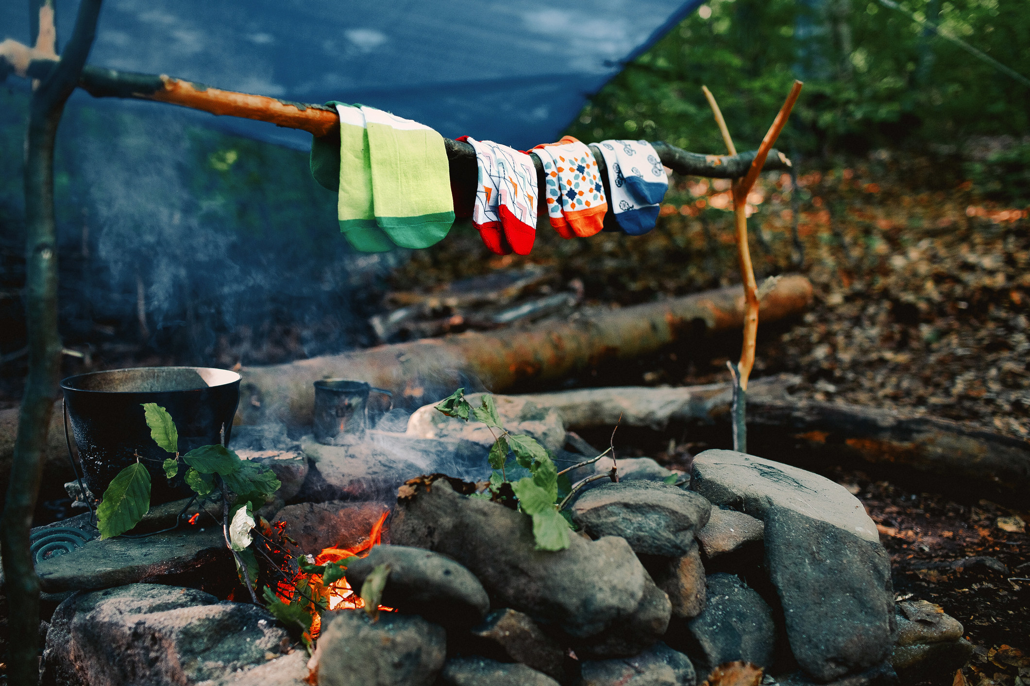 Four pairs of socks drying over a fire.